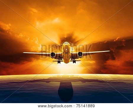 Passenger Jet Plane Flying Over Beautiful Sea Level With Sun Set Sky Above