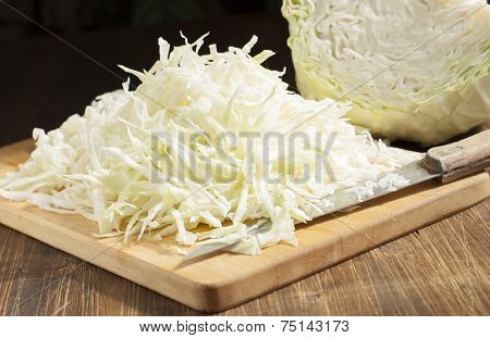 Chopped Cabbage Strips On A Cutting Board And A Head Of Cabbage.