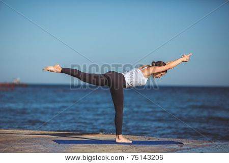 Young woman doing yoga on coast of sea on beach