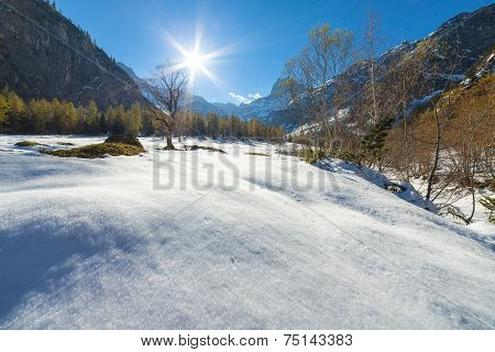 A scenic landscape with snow capped mountains in the late autumn season