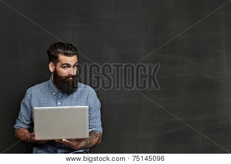 Bearded Man With Laptop Standing Near Chalkboard