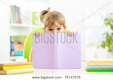 Cute child girl hiding behind book