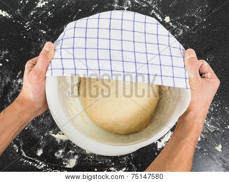 Person Covering A Dough For Proving In A Bowl On Black Table