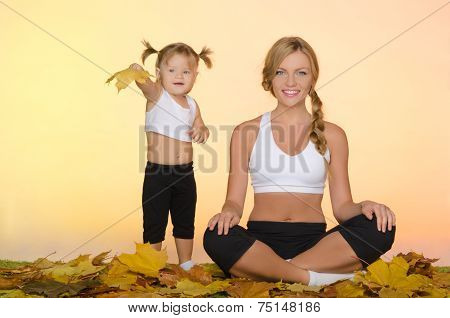 Beautiful Woman And Child Doing Yoga In Fall
