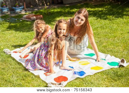 Mother And Girls Having Fun With Twister On Grass At Park
