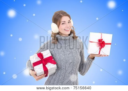 Happy Attractive Woman In Woolen Sweater And Muffs With Christmas Presents Over Winter Background