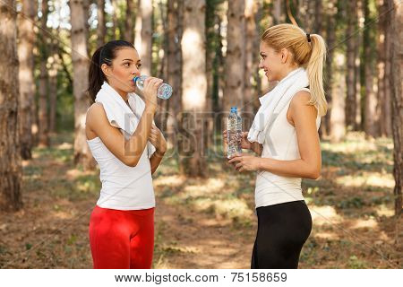 Two Beautiful Fitness Woman Drinking Water From Plastic Bottles