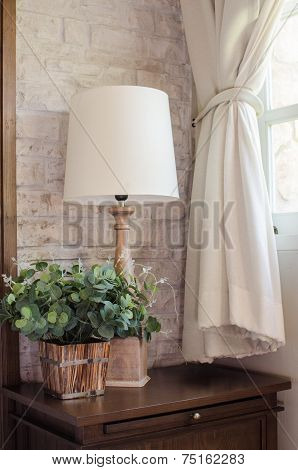 Bedside Lamp And Green Plant In Bedroom