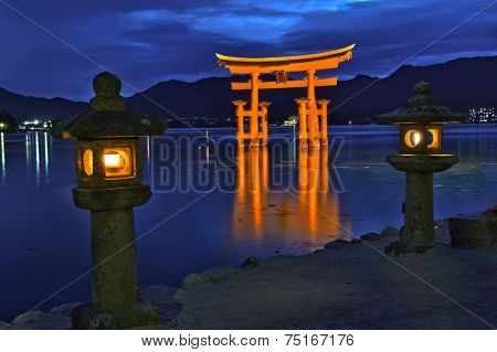Great floating gate (O-Torii) on Miyajima island near Itsukushima shinto shrine, Japan shortly after the sunset with lit lanterns on the shore