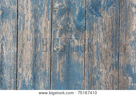 Old wooden barn board with distressed blue paint.