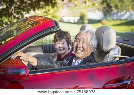 Attractive Happy Chinese Couple Enjoying An Afternoon Drive in Their Convertible.