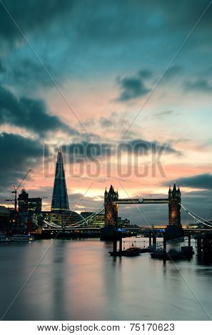 The Shard and Tower Bridge over Thames River in London at dusk.