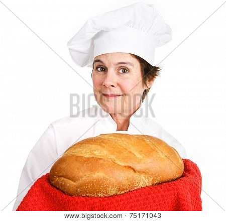 Pretty female bakery chef holding a loave of freshly baked bread, golden brown and crusty.  Isolated on white background.
