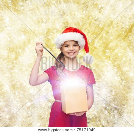 christmas, holidays, happiness and people concept - smiling girl in santa helper hat with gift box and magic wand over yellow lights background