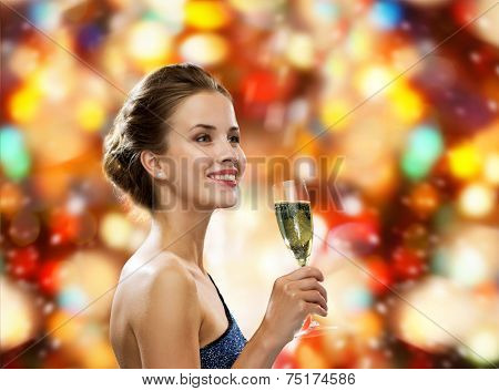 drinks, holidays, christmas, people and celebration concept - smiling woman in evening dress with glass of sparkling wine over red christmas lights background