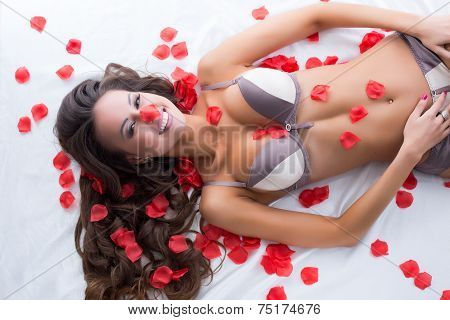 Cute lingerie model posing in bed with rose petals