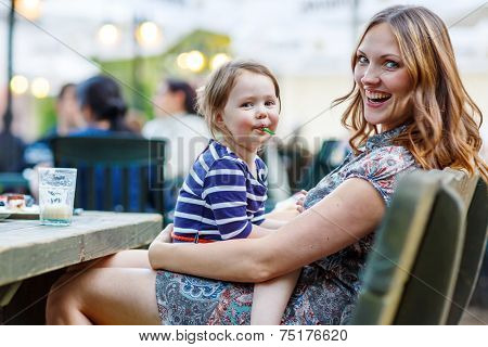 Mother And Little Adorable Kid Girl Drinking Coffee In Outdoor Cafe