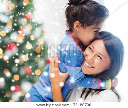 childhood, happiness, christmas, family and people concept - smiling little girl and mother hugging indoors over living room with tree