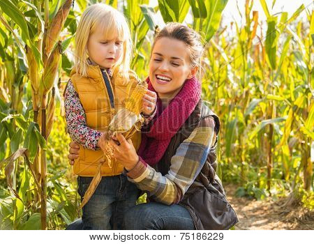 Portrait Of Mother And Child Shucking Corn In Cornfield
