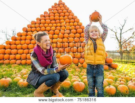 Portrait Of Happy Mother And Child Pumpkin In Front Of Pumpkin P