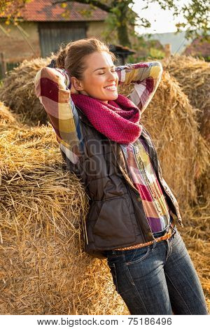 Portrait Of Relaxed Young Woman Near Haystack
