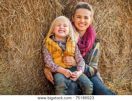 Portrait Of Happy Mother And Child Near Haystack