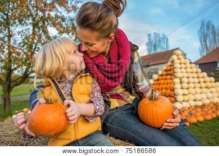 Smiling Mother And Child Sitting On Haystack With Pumpkins