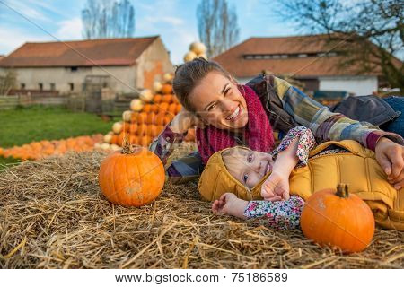 Smiling Mother And Child Laying On Haystack With Pumpkins