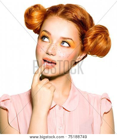 Beauty teenage Model Girl thinking or choosing. Beautiful Joyful teen girl with freckles, funny red hairstyle and yellow makeup . Professional make up. Isolated on a white background