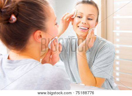 Fresh clean skin. Beauty teenage girl cleaning her face with cotton pad at home. Young happy brunette woman removing makeup from her face enjoying her skin and smiling at the mirror. Beauty skin care