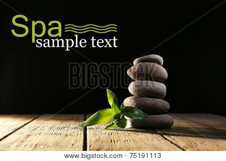Spa stones and bamboo on wooden table on dark background