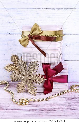 Holiday gift boxes decorated with vinous ribbon on table on wooden wall background