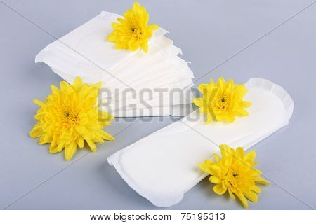 Sanitary pads and yellow flowers on light background