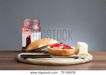 Bread Roll, Knive, Butter, Red Jam On Plate