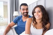 stock photo of pajamas  - Young couple lying in bed wearing pajamas - JPG