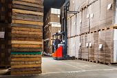 stock photo of lift truck  - Reach truck forklift lifting a pallet from the top shelf in a large warehouse - JPG