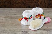 stock photo of booty  - baby booties and a brush for a newborn baby on a wooden background - JPG