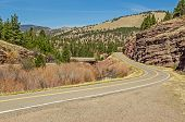 stock photo of mph  - Winding road with beautiful scenery and a 30 mph curve coming up on a Montana frontage road in spring - JPG