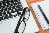 picture of field mouse  - Blank business laptop mouse pen note and glasses on wooden table  - JPG