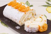 stock photo of satsuma  - Orange flavoured Swiss roll decorated with orange slices
