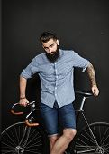 pic of bicycle gear  - Man with tattoo and bicycle on black wall background - JPG