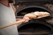 stock photo of wood craft  - introducing mass baker of bread in wood stove - JPG