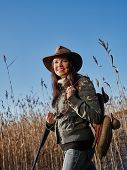 stock photo of shotgun  - Waterfowl hunting smiling female hunter carry a shotgun and a decoys reeds and blue sky on background - JPG