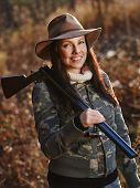 picture of shotgun  - Waterfowl hunting the female hunter carry a shotgun autumnal bushes on background - JPG