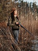 stock photo of shotgun  - Waterfowl hunting the female hunter loading the side by side shotgun shore and reeds on background - JPG