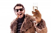 picture of hustler  - a young man wearing a sheepskin coat isolated over a white background holding a cigar and a glass with champagne - JPG