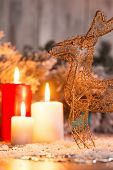 picture of deer family  - Christmas decoration   like wicker iron deer at red and white lightning candles  and fir branches  with selective focus - JPG