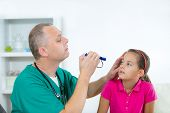 picture of ophthalmology  - Eye doctor examining young girl patient  - JPG