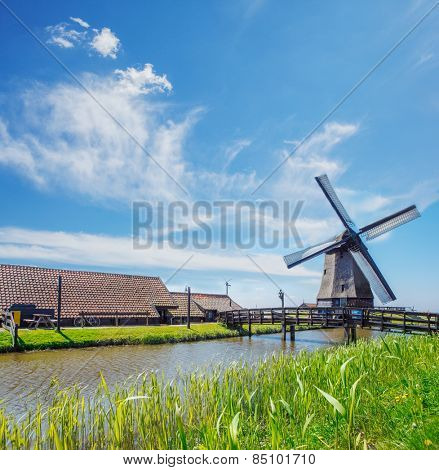 Old mill, farm houses and dyke, in the Netherlands, North Holland province
