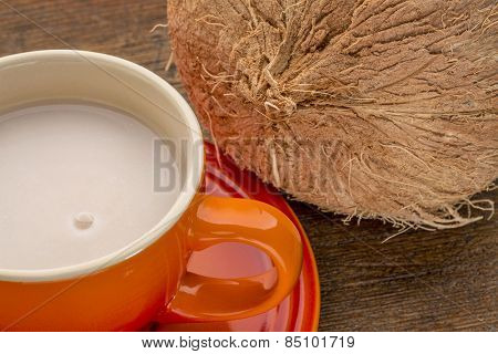 a stoneware cup of coconut milk with a coconut against wood background